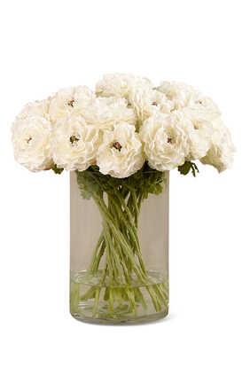 زهور حوذان صناعية في مزهرية زجاجية