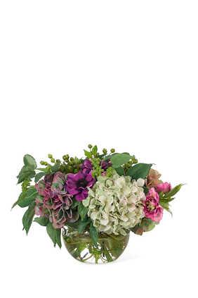 زهور هايدرنجا وشقائق النعمان في مزهرية زجاجية دائرية